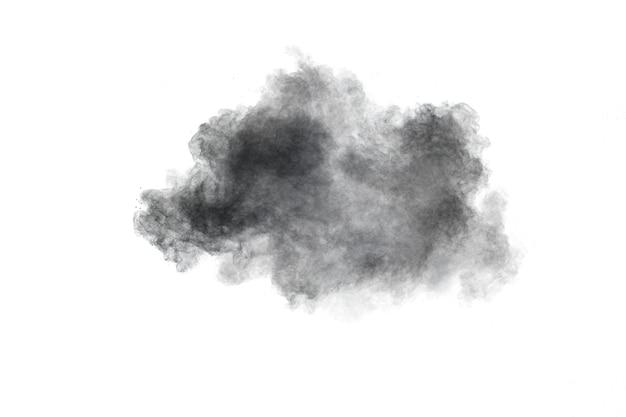 Explosión de polvo negro las partículas de carbón salpican sobre fondo blanco.