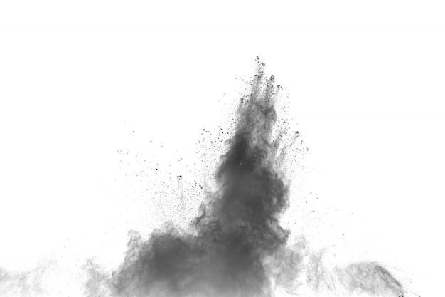 Explosión de polvo negro sobre fondo blanco. salpicaduras de partículas de polvo negro.
