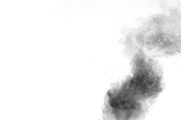 Explosión de polvo negro sobre fondo blanco salpicaduras de partículas de polvo negro.