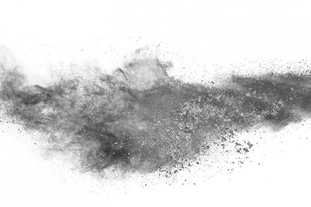 Explosión de polvo negro sobre fondo blanco.