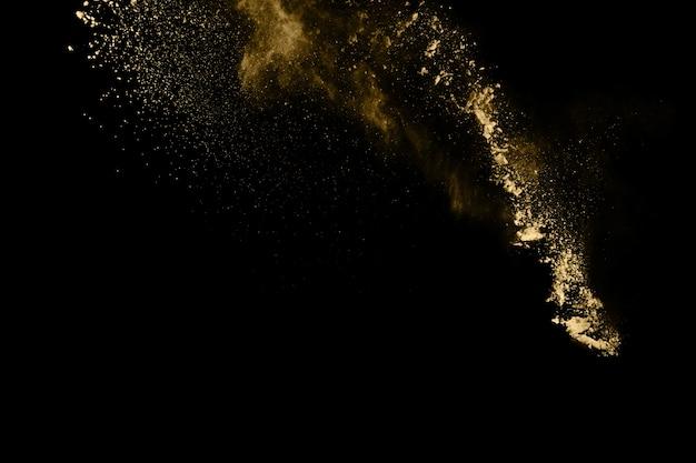 Explosión de polvo de oro sobre fondo negro. congelar el movimiento.