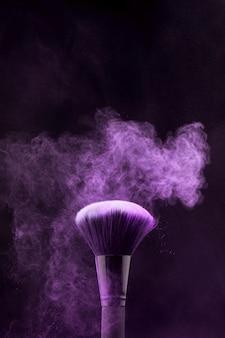 Explosión púrpura de maquillaje en polvo y pincel sobre fondo oscuro