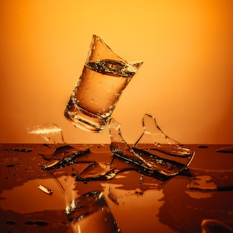 Explosión de la taza de vidrio con agua rompiéndose sobre la superficie naranja, choque y salpicaduras