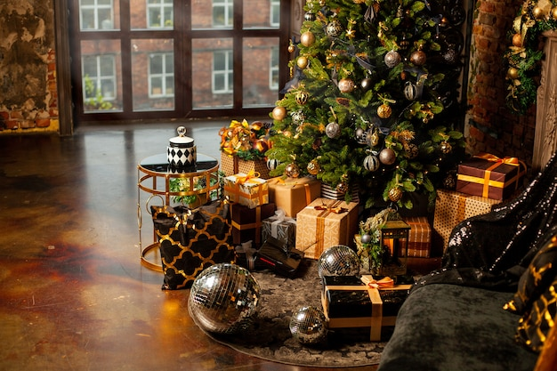 Exposición festiva de navidad en casa. árbol de navidad decorado con muchos regalos de colores dorado, marrón y negro y grandes bolas de discoteca plateadas