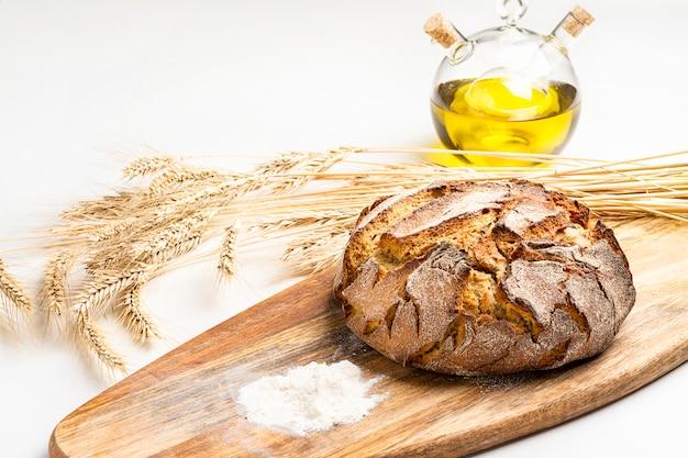 Exposición de pan casero fresco en la mesa de madera, sabroso desayuno. pan con aceite de oliva.