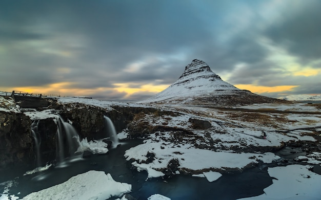 Exposición prolongada de montaña con primer plano de cascada en invierno