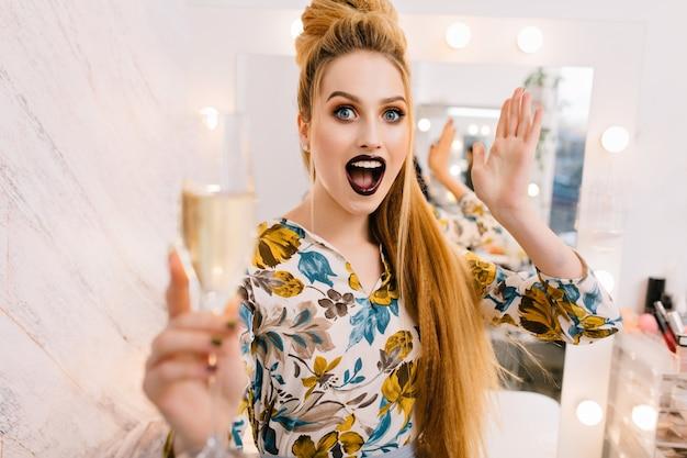 Expresando emociones brillantes de modelo bonita con estilo con peinado de lujo, maquillaje hermoso, copa de champán en salón de peluquería