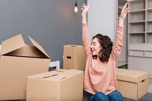Expresando emociones verdaderas brillantes, positividad de una mujer joven y bonita con el pelo rizado moreno corto en cajas de cartón envolventes de cama en apartamento moderno. disfrutando la mudanza, la felicidad en el nuevo hogar