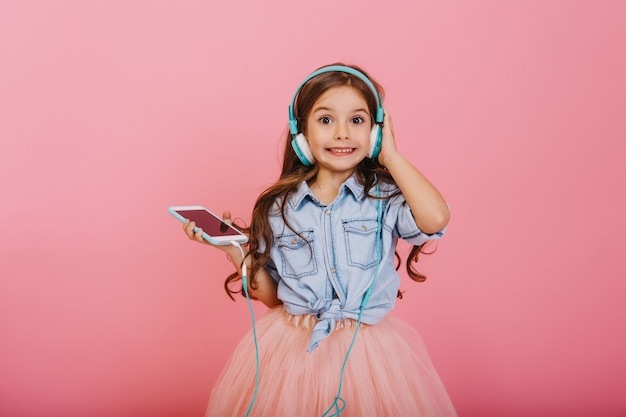 Expresando positividad de niño feliz escuchando música a través de auriculares azules aislados sobre fondo rosa. niña bonita con cabello largo morena sonriendo a la cámara en falda de tul