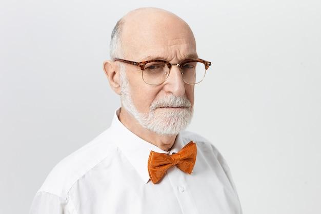 Expresión facial humana, actitud y percepción de la vida. retrato de hombre maduro calvo anciano serio molesto con arrugas en la frente y barba gris apretando los ojos, con mirada sospechosa