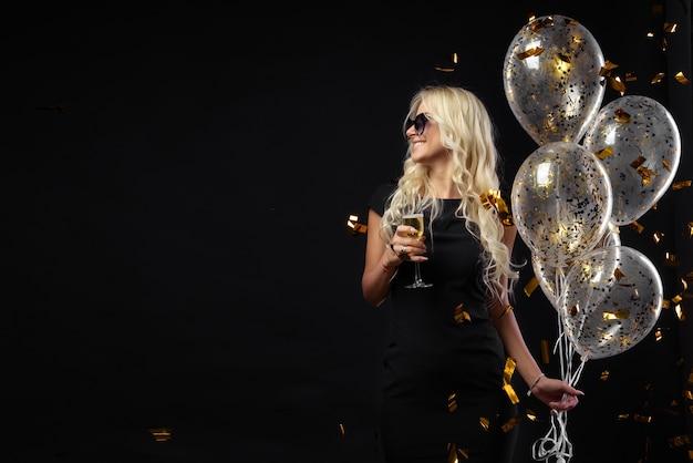 Expresiones brillantes de emociones felices de la increíble chica rubia celebrando la fiesta. vestidos negros de lujo, sonrientes, una copa de champagne, oropeles dorados, globos, cabello largo y rizado