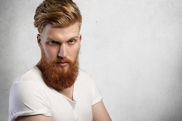 Expresiones y emociones del rostro humano. foto de cabeza de modelo joven con barba espesa posando con mirada enojada y antipática.