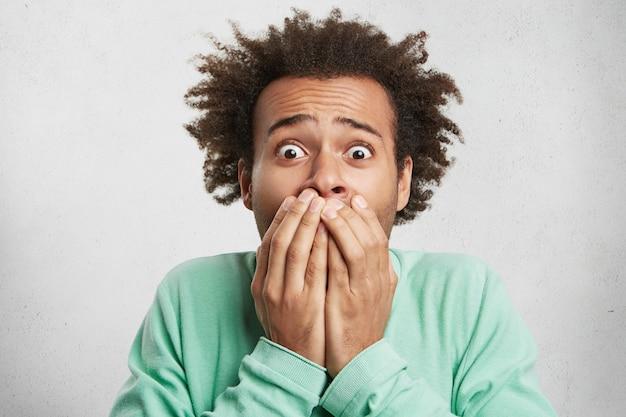 Expresiones, emociones y sentimientos faciales humanos. chico afroamericano mira con ojos saltones,