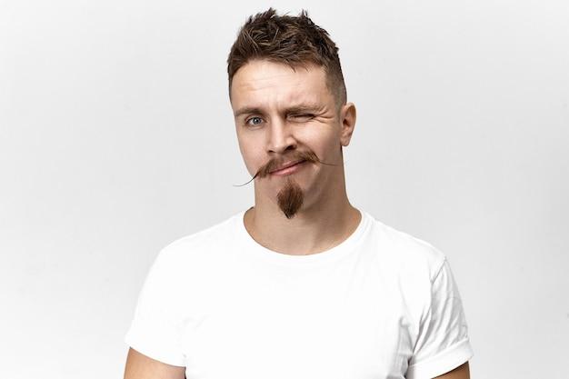 Expresiones faciales humanas y comunicación no verbal. atractivo joven hipster de moda con bigote de manillar y perilla posando aislado, parpadeando a la cámara, con mirada lúdica coqueta