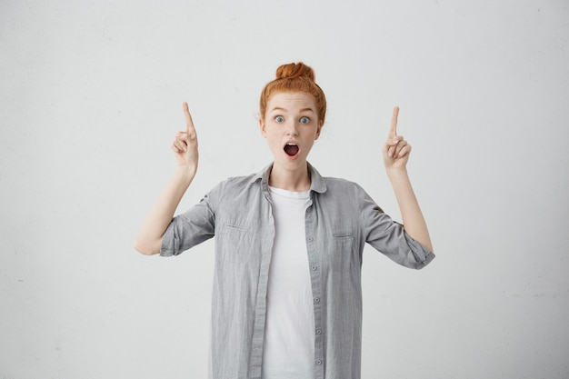 Expresiones faciales humanas, emociones, sentimientos, reacción y actitud. asombrada adolescente pelirroja vestida casualmente levantando ambas manos y señalando con el dedo hacia arriba, indicando algo por encima de su cabeza