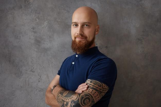 Expresiones faciales humanas, emociones, sentimientos, reacción y actitud. imagen de chico musculoso positivo con barba y tatuaje en el brazo posando aislado con los brazos cruzados, sonriendo felizmente