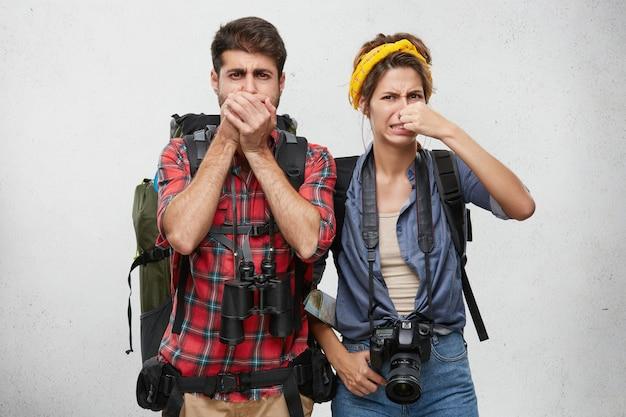 Expresiones faciales humanas, emociones y sentimientos. turismo y viajes. pareja joven activa en ropa turística, llevando mochilas, binoculares y cámaras fotográficas pellizcando las narices debido al hedor disgustado