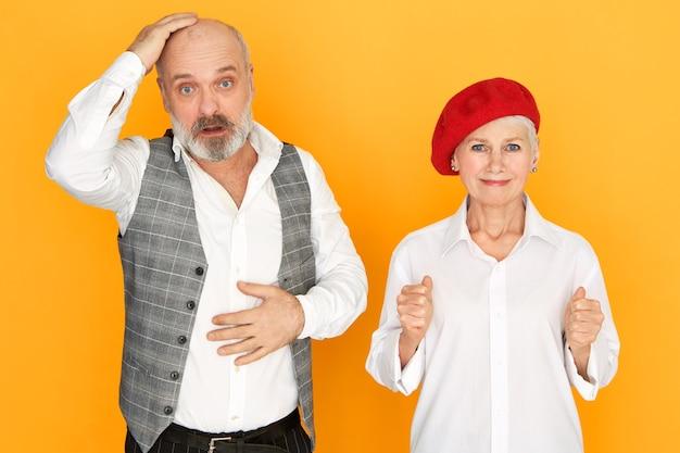 Expresiones faciales humanas y lenguaje corporal. imagen aislada de frustrado pensionista hombre barbudo tocando su cabeza calva con mirada perpleja, mujer madura esperanzada en el capó rojo apretando los puños
