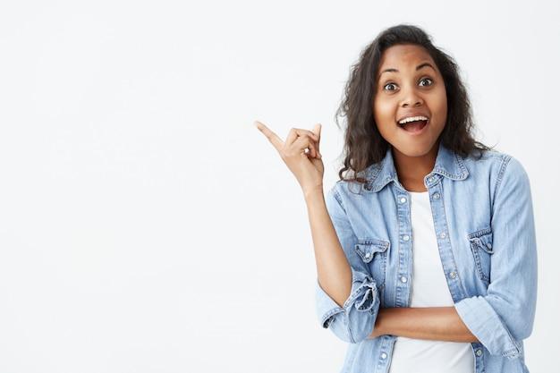 Expresiones de rostro humano, emociones y sentimientos. asombrada y sorprendida joven afroamericana en camisa de mezclilla celeste apuntando a la pared en blanco, sorprendida con los precios de venta, manteniendo la boca