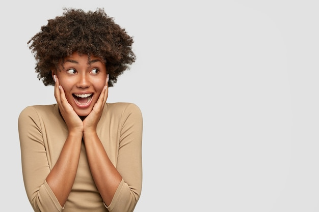 Expresiva atractiva mujer afroamericana exclama de felicidad, mantiene las manos en las mejillas, mira con alegría a un lado mientras nota que el mejor amigo regresa del extranjero, se para contra la pared blanca, espacio en blanco