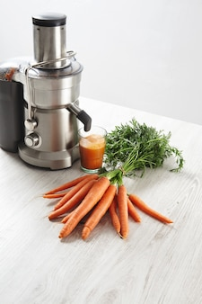 Exprimidor profesional metálico de vista lateral con vaso lleno de sabroso jugo para el desayuno de zanahorias de granja orgánica sobre mesa de madera.