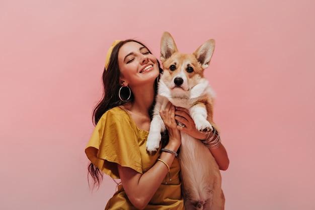 Exquisita chica con largo cabello ondulado en aretes redondos, pañuelo de moda y elegante vestido amarillo posando con los ojos cerrados y sonriendo