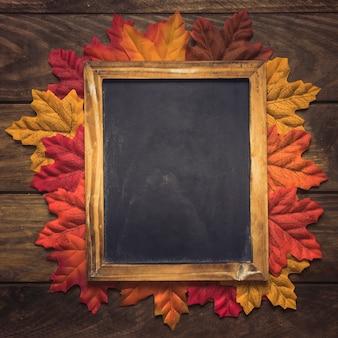 Exquisito marco de pizarra vacía con hojas de otoño