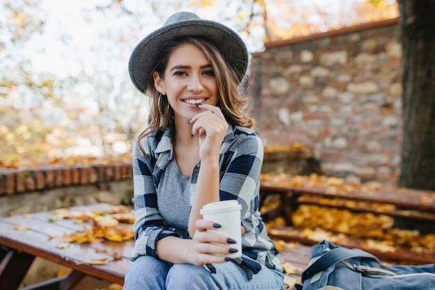 Extasiada mujer blanca en camisa casual sosteniendo una taza de té en el desenfoque de fondo de otoño