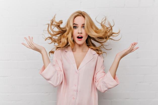 Extasiada mujer de ojos azules con largo cabello rubio posando delante de una pared de ladrillos blancos. filmación en interiores de una niña sorprendida en un hermoso pijama rosa.