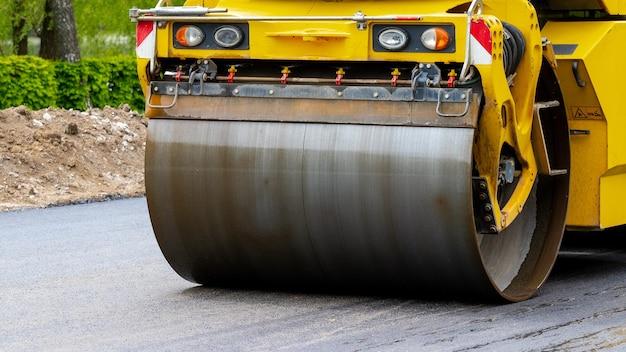 Extendedora de asfalto en la carretera durante la compactación de asfalto de cerca. reparación de carreteras. trazando un nuevo camino