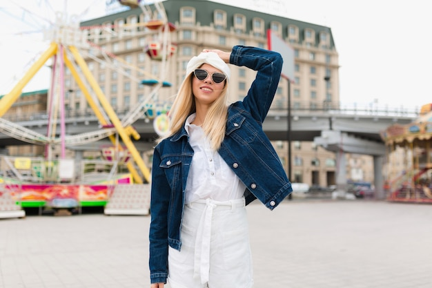 Exterior retrato de mujer elegante fashoin con cabello rubio vestido con blusa blanca y pantalones cortos. chaqueta de mezclilla y gafas blck caminando por la ciudad por un parque de atracciones en un día de verano