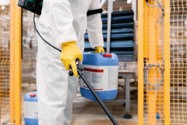 Exterminador en planta industrial rociando pesticidas con rociador. enfoque selectivo en la mano.