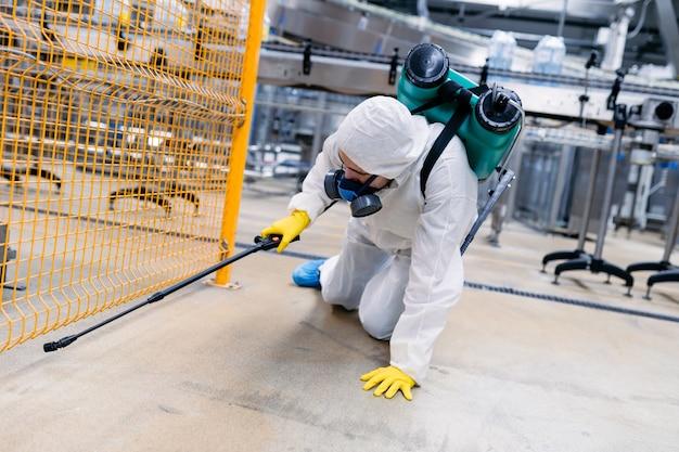 Exterminador en planta industrial rociando pesticidas con rociador