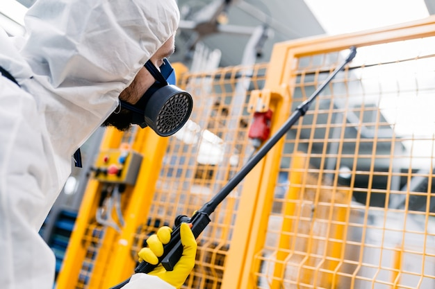 Exterminador en planta industrial rociando pesticidas con rociador.