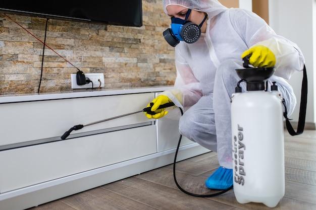 Exterminador en ropa de trabajo rociando pesticidas con rociador.