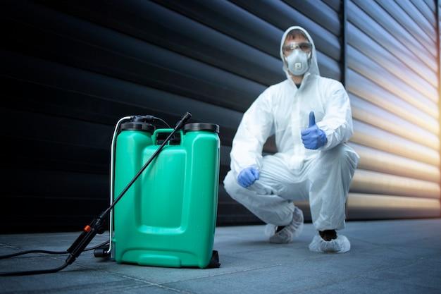 Exterminador en uniforme protector blanco de pie junto al depósito con productos químicos y pulverizador