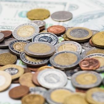 Extiende monedas metálicas sobre las notas de la moneda