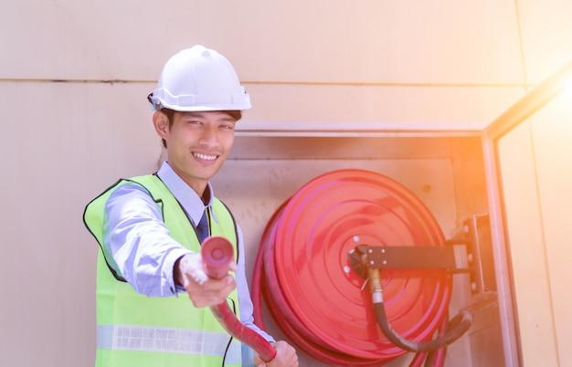 El extintor de incendios del ingeniero watercourse está listo para usar en el exterior.