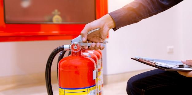 Extintor de inspección profesional masculino, concepto de seguridad.