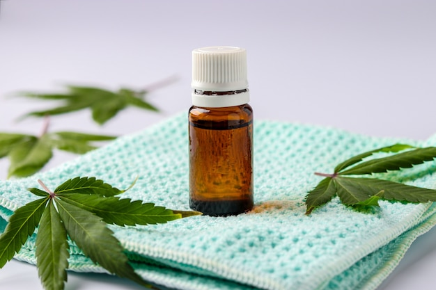 Extracto de aceite de cannabis en un frasco de vidrio ubicado sobre una superficie blanca con hojas de cáñamo, orientación horizontal, primer plano