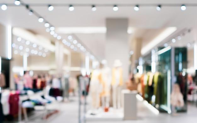 Extracto borroso del interior del boutique de la tienda de la ropa de la moda en alameda de compras