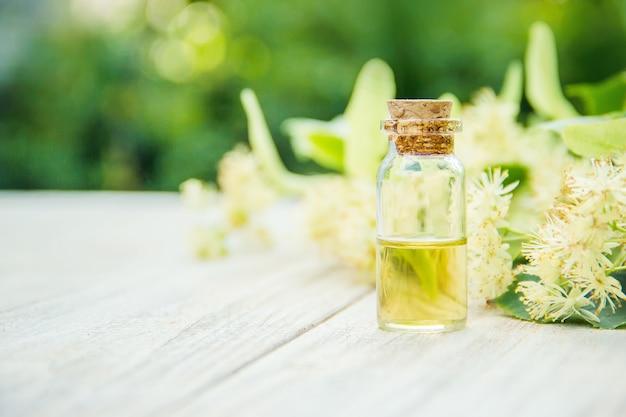 Extracto de linden y flores en una pequeña botella. enfoque selectivo