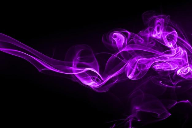 Extracto púrpura del humo en fondo negro y concepto de la oscuridad