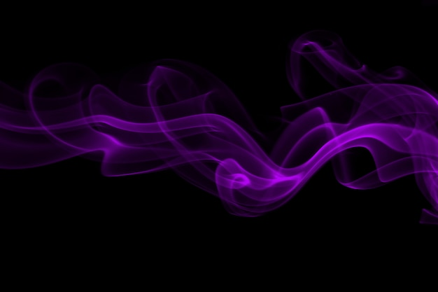 Extracto púrpura del humo en el fondo negro, concepto de la oscuridad