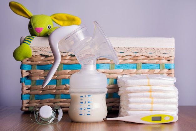 Extractor de leche, termómetros, pañales y un pezón de bebé con cesta de mimbre con un juguete.