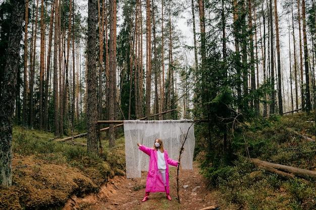 Extraña mujer joven con máscara y gabardina rosa posando con palo en el bosque
