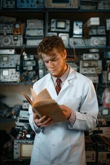 Extraño científico masculino leyendo un libro en el laboratorio. equipo de laboratorio, taller de ingeniería