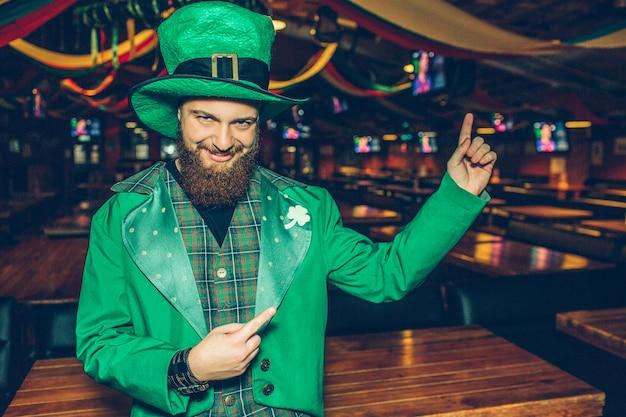 Extraño y feliz joven en traje verde de pie en el pub y señalar hacia atrás. él mira y posa. el tipo usa el traje de san patricio.