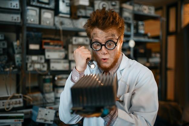 Extraño ingeniero examina el radiador de refrigeración, prueba en laboratorio. equipo de laboratorio, taller de ingeniería