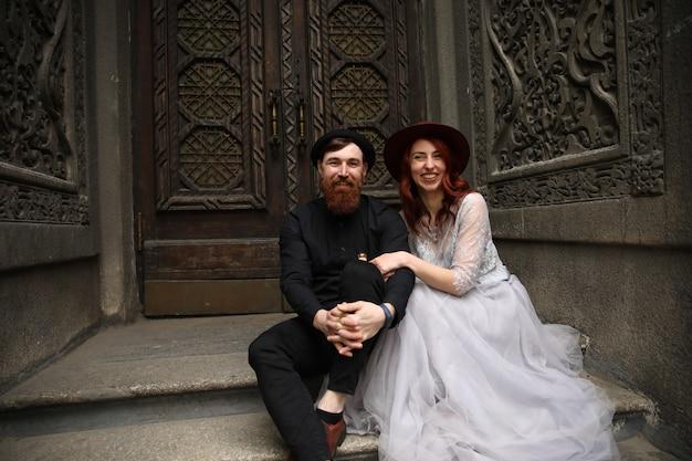 Extraordinaria pareja de novios vestida con sombreros y trajes formales está sentada en las escaleras de piedra y sonriendo